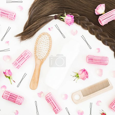 Tools for hair styling, shampoo and flowers on white background. Beauty composition. Flat lay, top view