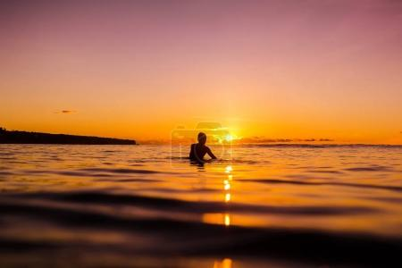 Beautiful young girl swiming in a tropical ocean at sunset