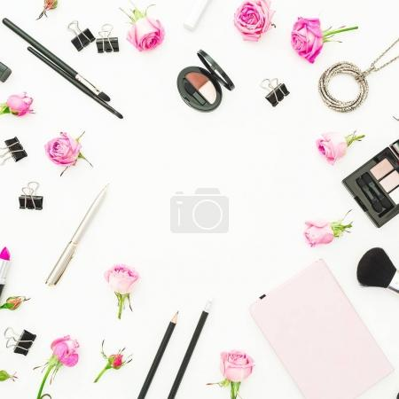Woman workspace with pink roses, cosmetics, diary on white background. Top view. Flat lay. Valentines day.