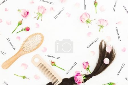 Frame with comb for hair styling, barrette and pink roses on white background. Beauty blog composition. Flat lay, top view