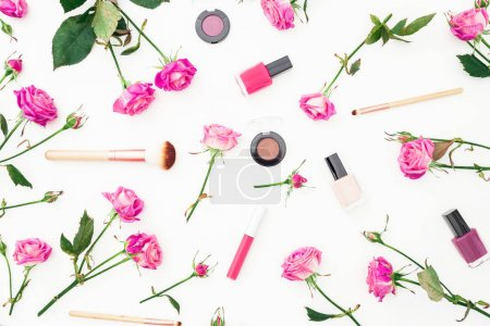 Beauty pattern with pink roses and cosmetics with accessories on white background. Woman's day background. Flat lay, Top view.