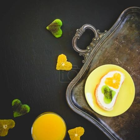 Sandwich with sugar cream, fruits and fresh juice. Flat lay, top view