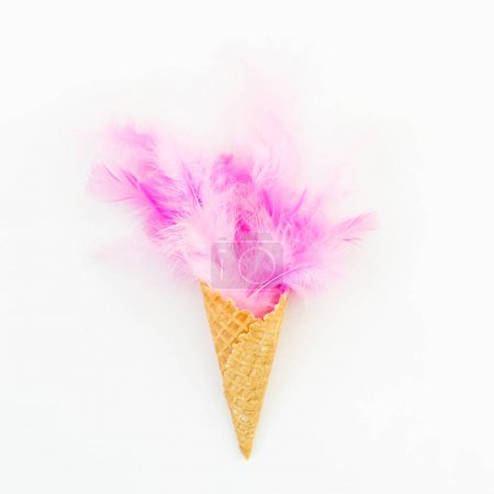 Pink feathers in waffle cone on white background. Flat lay. Top view.
