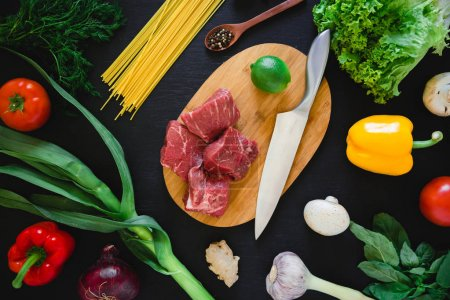 Photo for Food composition with raw meat on cooking board, knife, pasta and vegetables on dark table. Top view. Flat lay. - Royalty Free Image