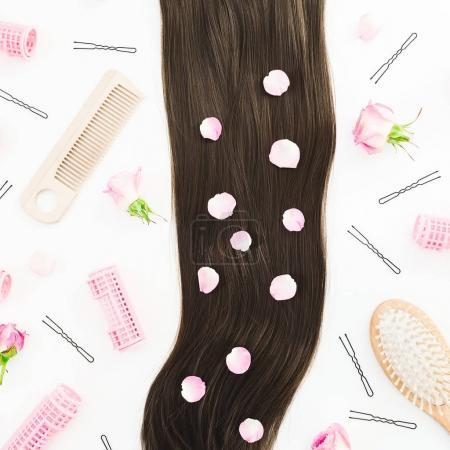 Cadre avec peignes pour coiffure et roses roses sur fond blanc. Composition de blog de beauté. Couché plat, vue du dessus