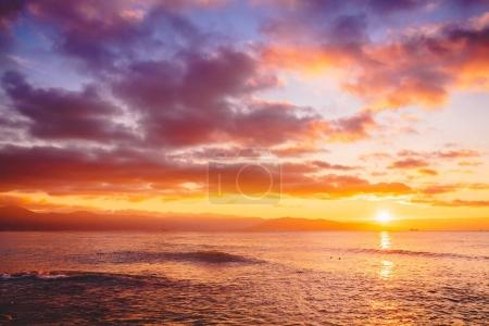 Bright sunset or sunrise in ocean. Landscape with warm sunset or sunrise colors