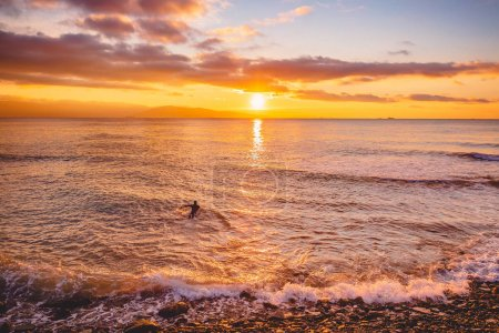 Surfer riding at sunset. Winter surfing in swimsuit