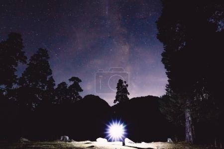 Photo for Milky Way, trees and silhouette of man with light in the mountains. Night landscape - Royalty Free Image