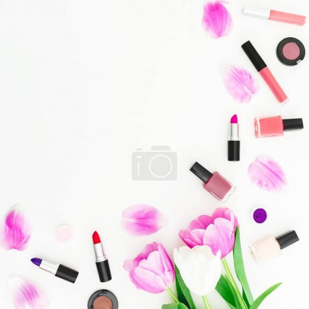 Frame of tulip flowers and cosmetics. Top view. Flat lay feminine desk.