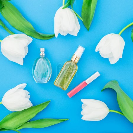 Photo for Top view of various cosmetic products with tulips on vibrant background - Royalty Free Image