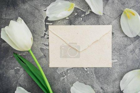 white envelope with white tulip on grey stone background