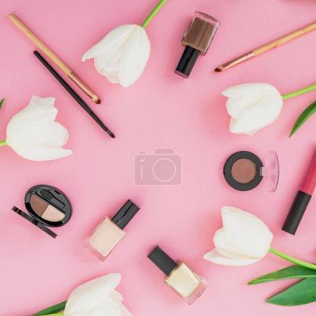 Photo pour Composition avec des produits cosmétiques et des tulipes blanches sur fond rose - image libre de droit