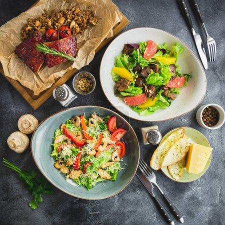 Vue de dessus de délicieuses viandes grillées au romarin et tomates sur une planche en bois avec les salades en plaques sur fond de table gris