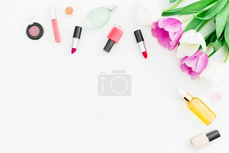 Photo for Top view of beautiful white flowers with bottles, lipstick and nail polish isolated on white background - Royalty Free Image