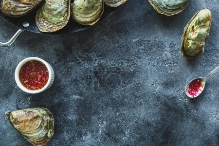 Top view of closed oysters with red sauce on grey background