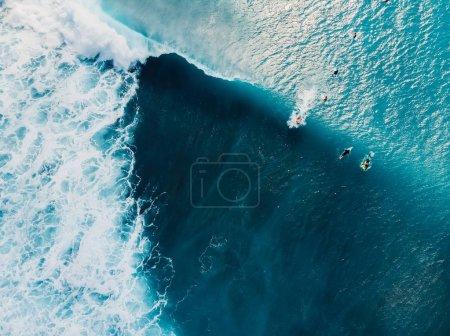 Luftaufnahme mit Surfern und Wellen im kristallklaren Ozean. Ansicht von oben