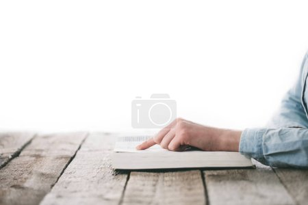 Hands reading a Bible and praying