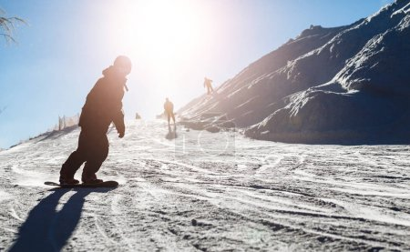 Snowboarder skating in the mountains with deep blue sky