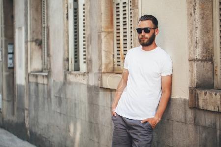 Photo pour Beau mannequin hipster avec barbe portant des t-shirt blanc blanc avec un espace pour votre logo ou un dessin dans un style urbain décontracté - image libre de droit