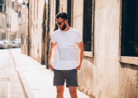 Photo for Hipster handsome male model with beard wearing white blank t-shirt with space for your logo or design in casual urban style - Royalty Free Image