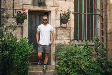Photo pour Hipster beau modèle masculin avec barbe portant blanc t-shirt blanc blanc avec de l'espace pour votre logo ou design dans un style urbain décontracté - image libre de droit