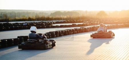 Karting competition or racing cars riding for victory on a racet
