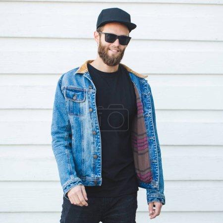 Photo pour Beau mannequin hipster avec barbe portant des t-shirt blanc noir avec un espace pour votre logo ou un dessin dans un style urbain décontracté - image libre de droit