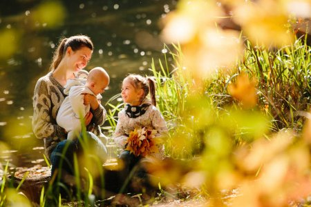 Happy family concept. Mother and children having fun in the autu