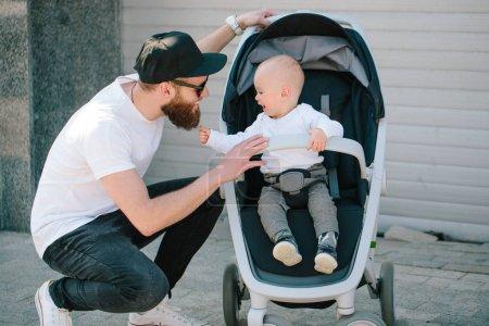 Père à pied avec une poussette et un bébé dans les rues de la ville