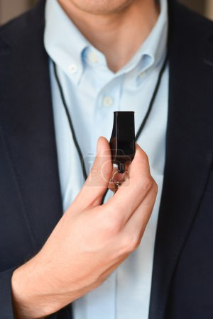 businessman in suit holding black whistle