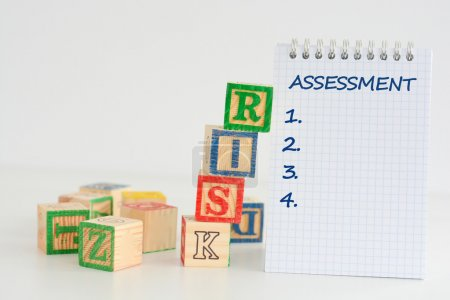 Photo for Risk assessment concept, risk lettering on wooden puzzle blocks and notebook with word assesment - Royalty Free Image