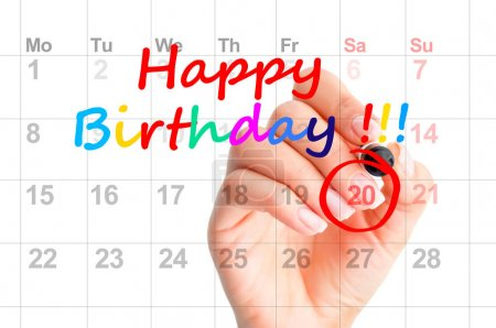 Happy birthday colorful text and a woman hand circling a date on a calendar