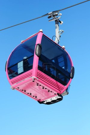 Pink cable car cabin over the snow mountain peak