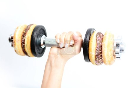 Healthy lifestyle concept suggested by weightlifting doughnuts
