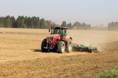 The tractor cultivates the soil in the spring