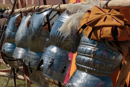 Hanged Metallic Armors in Line in front of Red and Yellow Tent