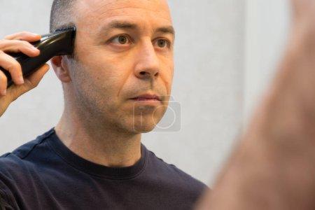 Photo pour Homme chauve avec Black chemise raser ses cheveux avec rasoir électrique devant un miroir. - image libre de droit