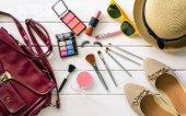 Kosmetika a oblečení pro ženy na bílé dřevěné podlahy
