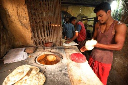 Photo pour DHAKA - BANGLADESH - 26 DÉCEMBRE 2016 : Un vendeur non identifié prépare du pain tandoor traditionnel sur le marché de Dacca, au Bangladesh - image libre de droit