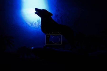 Photo pour Wolf en silhouette hurlant à la pleine lune. - image libre de droit