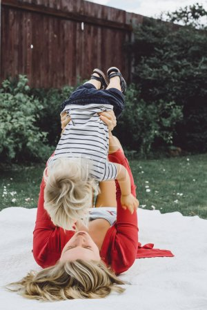 Mother having fun with her son on blanket