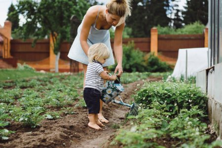 woman helping child watering plants