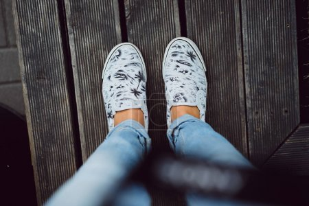 female legs in casual shoes with print