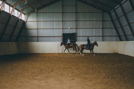 Photo pour Deux femmes en tenues de sport et de casques à cheval dans une arène - image libre de droit