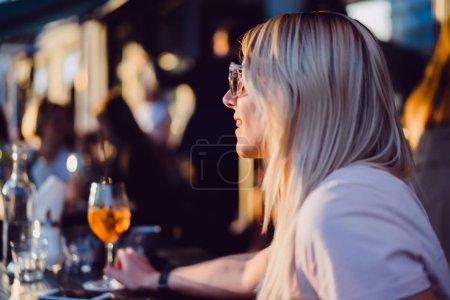 femme assise en terrasse en plein air