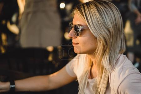 blonde woman in sunglasses in outdoor cafe
