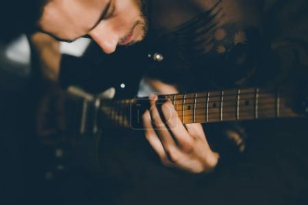 Photo for Cropped image of young man playing electric guitar at home - Royalty Free Image