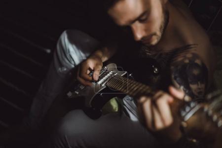 Mann spielt zu Hause Gitarre