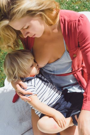 young mother Feeding cute blonde boy on green grass outdoor at summer