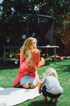 cute blonde boy with young mother using soap bubbles on green grass outdoor